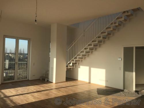 großes, helles Wohnzimmer mit Treppe zum Obergeschoss